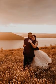 Ein liebendes paar, das jungvermählten in weißem kleid und anzughochzeit umarmt, küsst wirbel auf hohem gras im sommerfeld auf berg über dem fluss