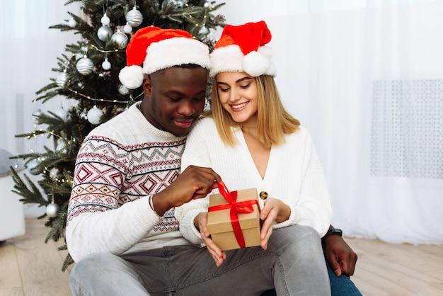 Ein liebendes paar, das lacht und ein weihnachtsgeschenk hält und lächelt