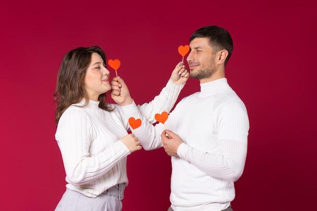 Ein liebendes paar, das mit roten papierherzen auf rotem hintergrund aufwirft. zeit am valentinstag verbringen