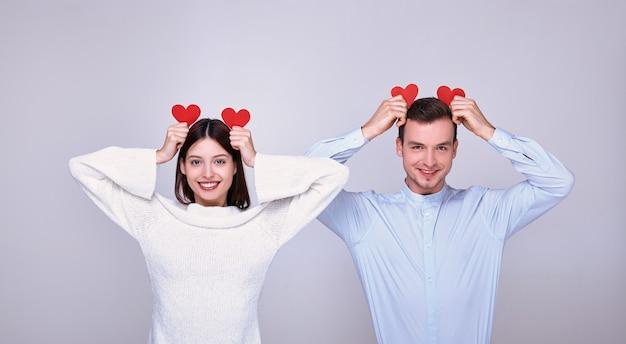 Ein liebes liebespaar mit verspielter stimmung zum valentinstag hält beide zwei rote pappherzen in der hand