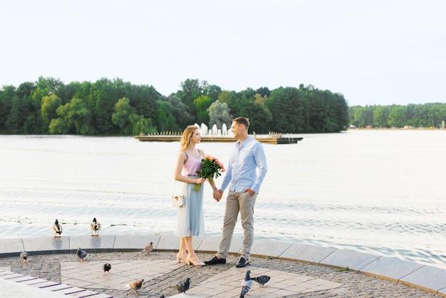 Ein liebespaar ein mann und ein mädchen halten sich an den händen und stehen an einem fluss oder see in einem stadtpark