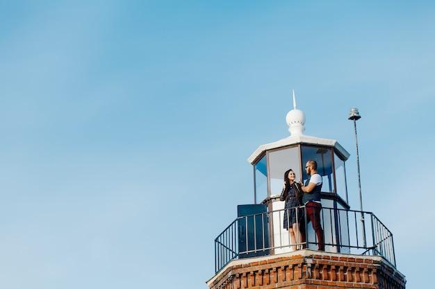 Ein liebespaar umarmt sich oben auf einem leuchtturm
