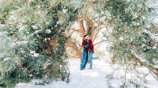 Ein liebevolles junges paar ruht in den bergen in einem schneebedeckten wald. konzept der gemeinsamen ruhe