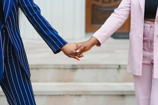 Ein liebevolles lesbisches paar, das händchen hält. hände zusammen zwei afrikanische lesbische mädchen