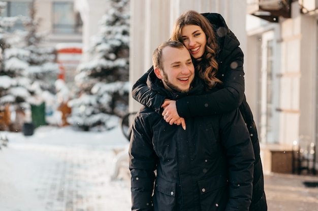 Ein liebevolles paar in einer sanften umarmung vor dem hintergrund einer verschneiten stadt. hochwertiges foto