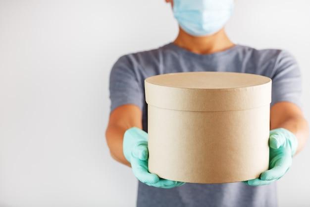 Ein lieferservice kurier in gummihandschuhen und eine maske hält das paket.