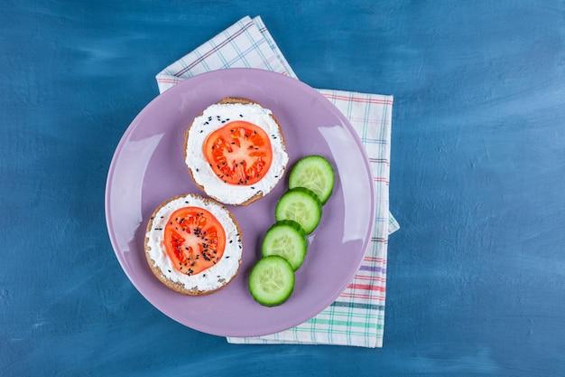 Ein lila teller mit geschnittenen gurken und sandwiches mit käse und geschnittenen tomaten.