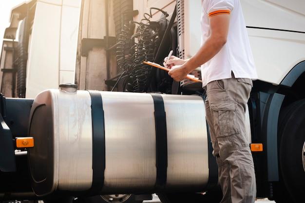 Ein lkw-fahrer, der die zwischenablage hält, überprüft täglich seine sicherheit eines großen kraftstofftanks eines sattelschleppers. güterverkehr.