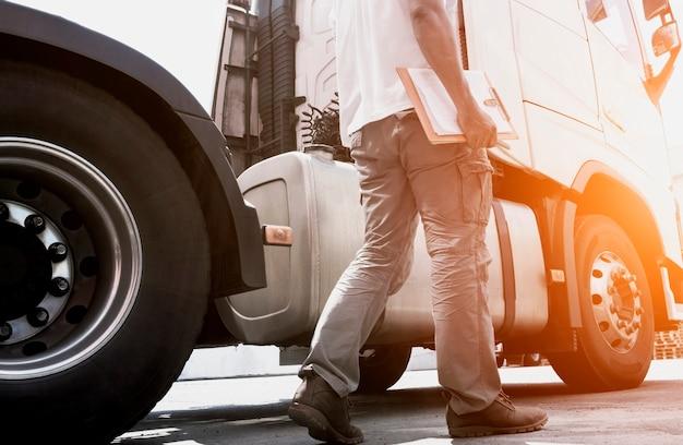 Ein lkw-fahrer hält die zwischenablage seines täglich überprüfenden sicherheits-sattelschleppers, güterverkehr.