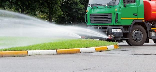 Ein lkw zum bewässern des rasens gießt mit wasserstrahlen wasser auf den rasen. rasenpflege in der stadt.