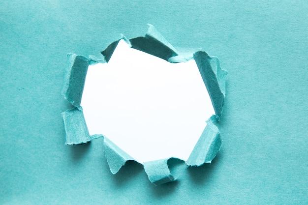 Ein loch in papier mit abgerissenen seiten. zerrissenes papier. mit platz für ihre nachricht