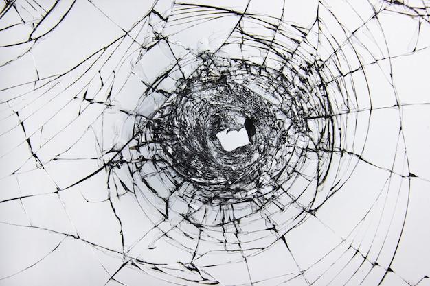 Ein loch und risse in glasscherben auf einem fenster aus windschutzscheiben-autoglas. transparente windschutzscheibe eines autos mit einem loch nach den schüssen.