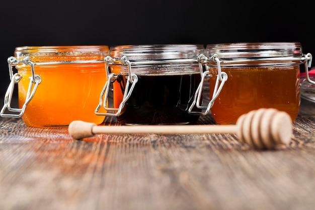 Ein löffel für honig zusammen mit hochwertigem bienenhonig, ein alter tisch auf dem ein gesunder und süßer bienenhonig steht und ein hölzerner speziallöffel