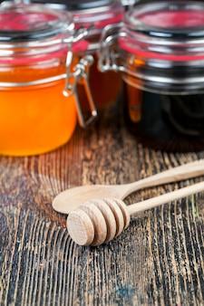 Ein löffel für honig zusammen mit hochwertigem bienenhonig ein alter tisch, auf dem ein gesundes und s...