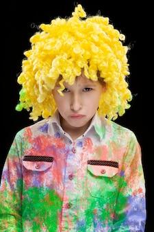 Ein lustiger junge in einer gelben clownperücke und bunter kleidung mit traurigem gesicht.