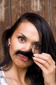 Ein lustiges brunettemädchen mit dem schnurrbart
