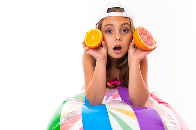 Ein lustiges kaukasisches mädchen mit langen haaren, badeanzug, weißer kappe hält grapefruit und orange hälften