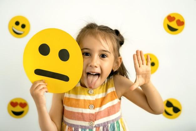 Ein lustiges mädchen hält ein trauriges emoticon aus pappe in den händen und zeigt ihre zunge beim lachen