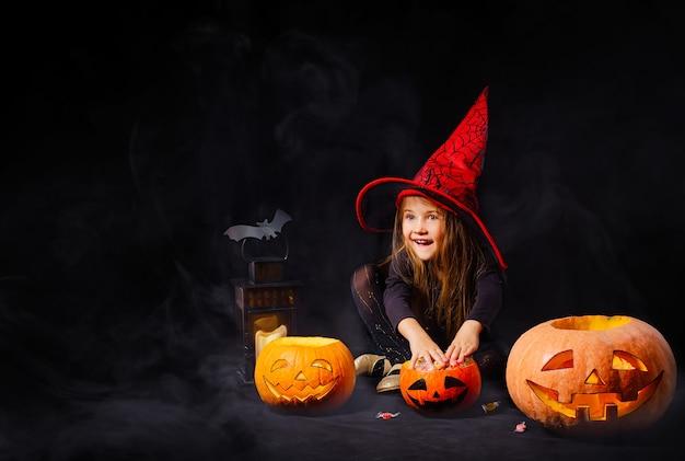 Ein lustiges mädchen im karnevalskostüm einer kleinen hexe spielt mit kürbissen und süßigkeiten im zimmer.