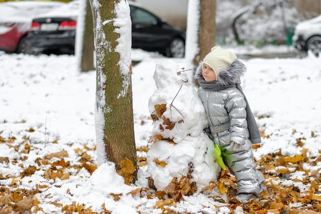Ein lustiges mädchen in einem silbernen overall hält eine spielzeugschaufel und formt einen schneemann