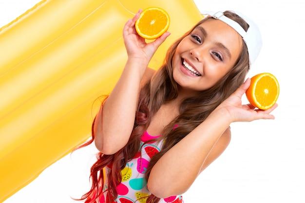 Ein lustiges mädchen mit langen haaren, badeanzug und weißer mütze steht in der nähe von aufblasbaren matratzen, hält orangefarbene hälften und lächelt