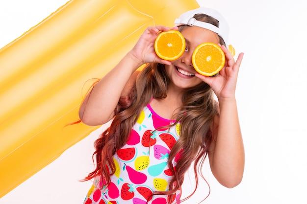 Ein lustiges mädchen mit langen haaren, badeanzug und weißer mütze steht in der nähe von aufblasbaren matratzen und trägt orangefarbene hälften auf augen und lächeln auf