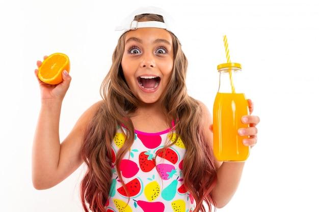 Ein lustiges mädchen mit langen haaren, badeanzug, weißer mütze, hält orangenhälfte, orangensaft und schreit freudig
