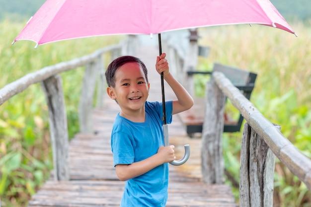Ein lustiges spielen des jungen mit regenschirm