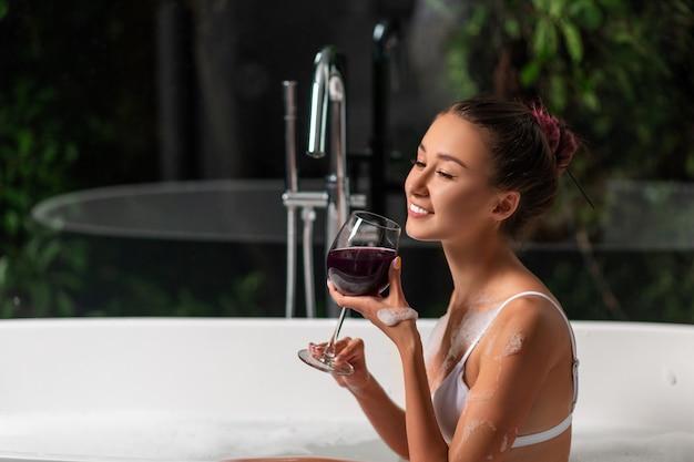 Ein luxuriöses mädchen entspannt sich in einem schaumbad mit einem glas wein. spa und entspannung