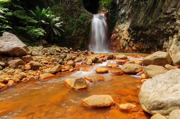 Ein mächtiger wasserfall, der im fluss nahe felsformationen in dumaguete, philippinen fließt