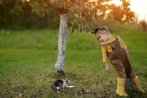Ein mädchen als obdachloses kätzchen trinkt milch aus einer schüssel
