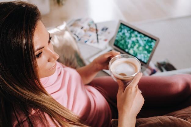 Ein mädchen am morgen im pyjama zu hause, das an einem laptop mit kaffeetrinken arbeitet, ein mädchen, das zu hause selbst isoliert ist und sich auf der couch ausruht und einen laptop beobachtet. hausarbeit.