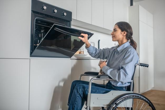 Ein mädchen auf einem rollstuhl, der den ofen in der küche öffnet, während er etwas kocht
