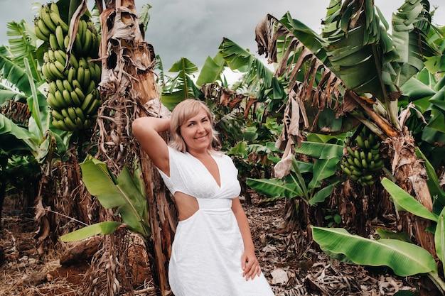 Ein mädchen auf einer bananenplantage auf der insel mauritius, eine bananenfarm auf einer tropischen insel, ein mädchen in einem weißen kleid auf einer plantage in afrika.