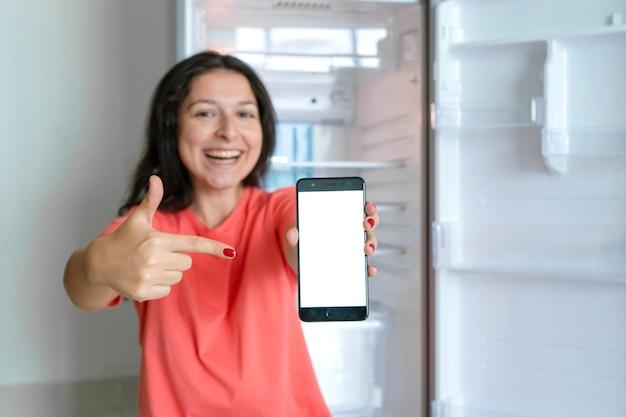 Ein mädchen bestellt essen mit einem smartphone. kühlschrank ohne lebensmittel leeren. werbung für lebensmittel-lieferservice.