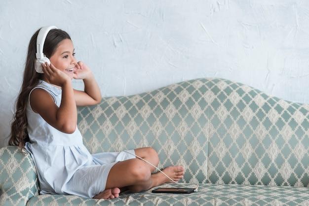 Ein mädchen, das auf hörender musik des sofas auf dem kopfhörer befestigt am handy sitzt