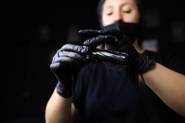 Ein mädchen, das ein meister des permanent make-ups ist, hält eine tätowiermaschine vor sich und zieht eine zusätzliche schutzfolie darüber film