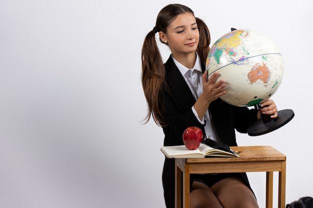 Ein mädchen, das ein modell des globus hält, betrachtet es isoliert auf weißer leerstelle