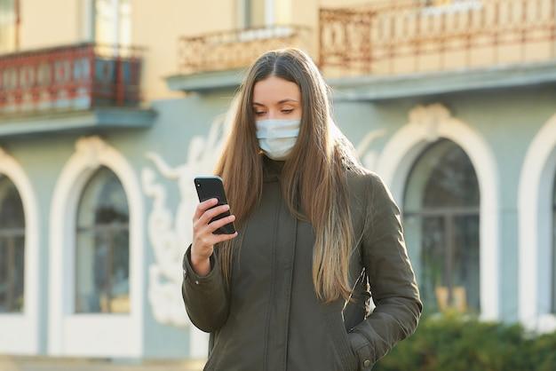 Ein mädchen, das ein smartphone benutzt, trägt eine medizinische gesichtsmaske, um die ausbreitung des coronavirus auf einer stadtstraße zu vermeiden