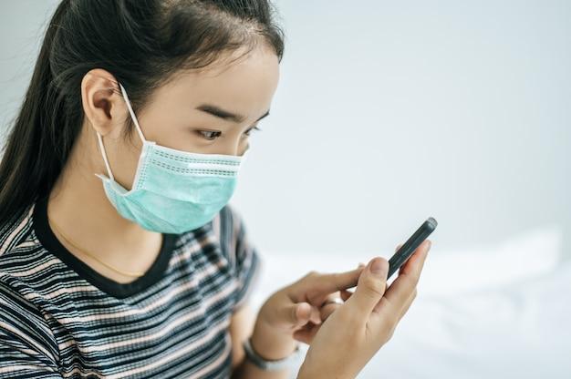 Ein mädchen, das eine maske und ein gestreiftes hemd trägt, das ein smartphone spielt.