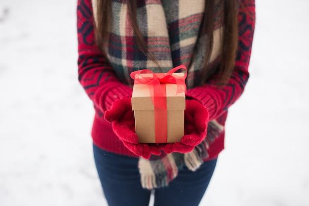 Ein mädchen, das im winter ein geschenk in ihren händen auf der straße hält