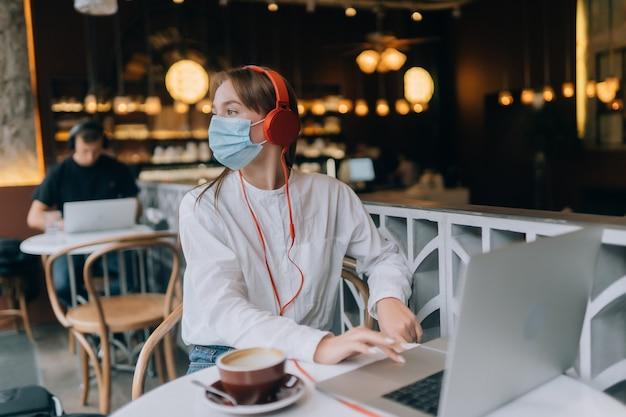 Ein mädchen, das in einem café mit kopfhörer-coronavirus-ausbruch sitzt