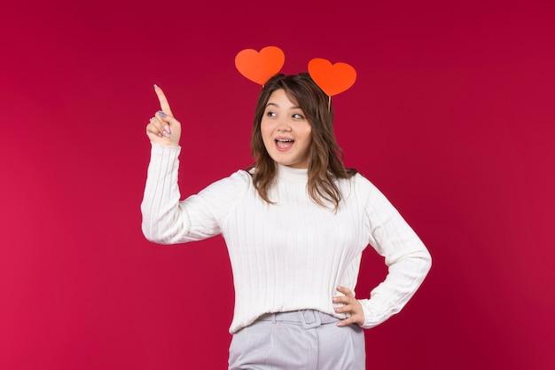 Ein mädchen, das in wow-emotionen verliebt ist, zeigt seinen zeigefinger nach oben. überraschtes mädchen auf rotem hintergrund