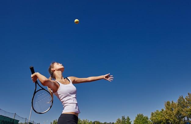 Ein mädchen, das tennis auf dem platz an einem schönen sonnigen tag spielt