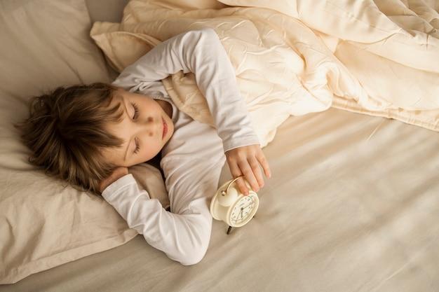 Ein mädchen, ein weibliches kind, liegt ruhig in einem bett mit einem wecker in den händen. die sonne scheint aus dem fenster