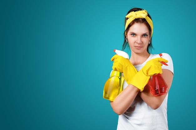 Ein mädchen eine putzfrau mit einem reinigungsmittel, das handschuhe und einen lappen trägt