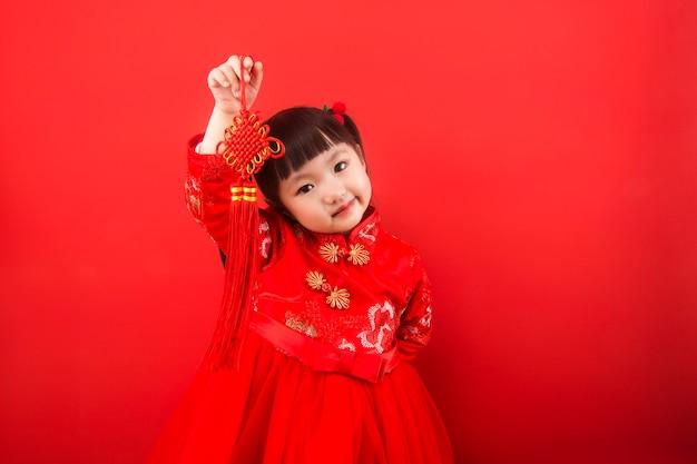 Ein mädchen feiert das chinesische neujahr mit einem chinesischen knoten