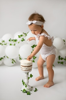 Ein mädchen feiert ihren geburtstag. das kind war ein jahr alt. das kind isst seinen ersten kuchen. das dekor besteht aus luftballons und efeu.