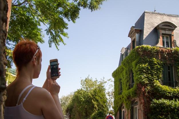 Ein mädchen fotografiert am telefon ein überwuchertes haus in der altstadt von montmartre in paris