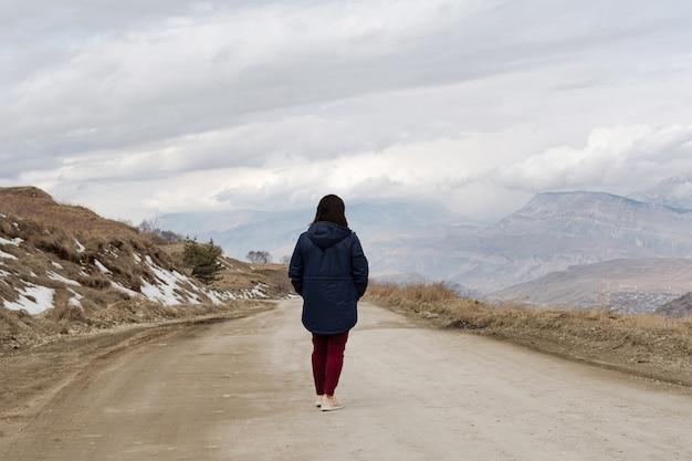 Ein mädchen geht entlang einer hochgebirgsstraße gegen einen düsteren himmel mit wolken und bergen
